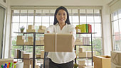 Asian business woman giving a gift. Postal parcel packaging carton box delivery, working from home, selling products online business. Shipping service. People lifestyle in coronavirus pandemic.