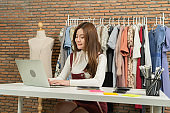 An Asian woman girl working online from home, selling fashion shirts clothes casual wear, using laptop device for communication in technology social media. Online shopping business. SME ecommerce.