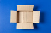 One empty open brown cardboard box on blue background. Top view