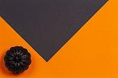Minimal Halloween background. Decorative black shiny pumpkin on orange and black background. Top view