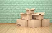 Cardboard boxes in front of a green colored stone wall stock photo
