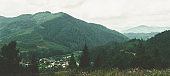 Panorama mountain landscape, view from mountain to small village located in lowland. Mountain slopes overgrown with vegetation