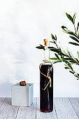 A bottle of strong alcoholic drink with a green olive branch on a light background. Minimalistic still life bottle of homemade liquor or tincture