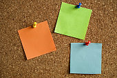 Colored Note Papers Fastened To Cork Board