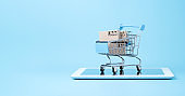 Isolated of Shipping paper boxes inside blue shopping cart trolley on tablet with blue background and copy space , Online shopping and e-commerce concept.