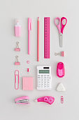 Pink school stationery on a grey background. Top view. Flat lay. Back to school concept.