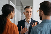 Confident mentor or business coach teaches people at business seminar, explaining information. Colleagues planning start up, talking, cooperation, working in office. Meeting, teamwork concept