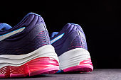 Cushioned running shoes. Female sneakers for run on dark background. Fashion stylish sport shoes, close up