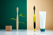 Zero waste, Eco-friendly creative concept. Wooden bamboo toothbrush with leaves VS plastic brush. Natural organic bathroom beauty product.