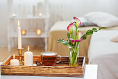 cup of tea and flowers on wooden tray indoor