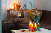 burning candles with autumn decor on white table at home