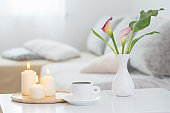 cup of coffee and flowers in vase on white table indoor