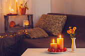 autumn decorations with burning candles at home