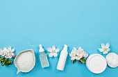 Clean pure spring beauty products background. White objects moisturizing creams, pipette oil bottle, bath salt in bowl. Flat lay blue background, white tender apple tree blossoms. Lot of copy space.