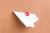 paper plane and stop sign in it, cork board, prohibition of flights and travel during the coronavirus epidemic, space copy, wooden background, closing borders concept