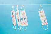 several childish medical protective masks with drawings hang on a rope on a blue background, copy space, virus protection, coronovirus epidemic