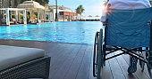 Wheelchair broken leg woman sit along pool resort and travel outdoor