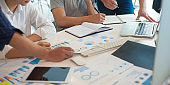 A group of young business people analyzes strategies and plans for marketing. The analyst team convenes a brainstorming session for data analysis and business strategy planning together.