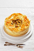 Layered Apple Pie With Phyllo Crust on a white platter on a white wooden table, vertical view from above