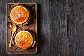 chicken pot pie in the rustic clay pots on a rude wooden board with wooden spoons, flat lay, free space, horizontal view from above, english cuisine
