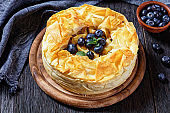 Layered Apple Blueberry Pie With Phyllo Crust on a dark rustic wooden table, horizontal view from above, close-up
