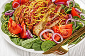 spinach tomato onion salad topped with baked chicken breast sprinkled with lemon zest on a white platter on a white textured wooden table, horizontal view from above, american cuisine, close-up