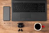 Desk top view. Laptop, Cup, Earphones and smartphone on the wooden desk.