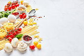 Food background with place for text, with different kinds of pasta, tomatoes, herbs, mushrooms, eggs, seasonings scattered on light marble background.