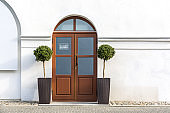 closed red wooden door with two trees in pots on a white wall