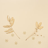 Autumn composition with autumn leaves of rowan in gold color on neutral beige background. Fall time concept
