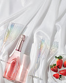 Rose champagne in bottle, bright glasses for wine and and red berries strawberry sparkling on light with beautiful shadows