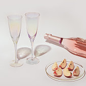 Ð¡losed bottle of rose champagne sparkling wine and glasses, pieces of apple fruit with sunlight on light table
