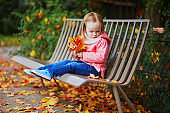 Adorable toddler girl sitting on the bench and gathering fallen leaves in autumn park