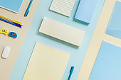 Stationary school supplies in yellow and blue tone. Office accessories on paper background.