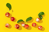 Frame from ripe small red apples and green leaves with dark shadows on yellow color background.