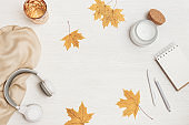 Autumn flat lay home relaxation with notebook for sketches and headphones, glass of water, aromatic candle