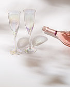 Ð¡losed bottle of rose wine and two crystal glasses with sunlight and natural shadow