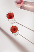 Rose wine in bright crystal glasses, rose champagne sparkling wine with daylight shadows. Summer alcoholic drink