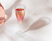 Bottle of rose champagne sparkling wine and beatiful bright glasses with sunlight on light table
