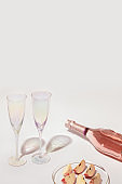 Ð¡losed bottle of rose wine and two crystal glasses, pieces of apple fruit on transparent plate