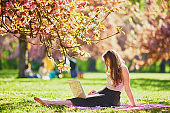 Beautiful young girl working on her laptop in park during cherry blossom season
