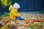 Adorable toddler girl sitting on the ground and playing with yellow fallen leaves in autumn park
