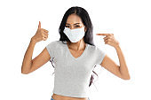 Portrait of an Asian woman wearing a medical flu mask to protect against coronavirus. She showed a happy expression and pointed her finger at the face. Isolated on white background