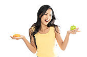 Portrait of an Asian woman holding a green apple and donut in both hands. She chose between a weight loss diet and a high-fat diet. isolated on white background