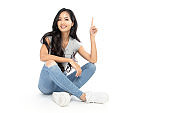 A young Asian woman wore a casual dress sit on the floor. She pointed her finger at the copy space on the top. Isolated on white background