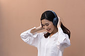 Portrait of a beautiful Asian woman with healthy skin. She was wearing a white sweater. She listened to music on the headphones and danced with joy. isolated on brown background