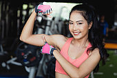 Close up side view. Portrait of asian young woman showing muscles of the arm in fitness gym .She has a smiling face.