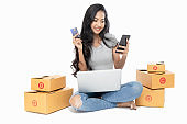Portrait of an Asian woman sitting on the floor with a lot of boxes beside. She uses a laptop and credit card to buy products and services from home. Shopping online concept. She smiled Isolated on white background