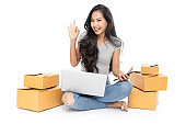 Portrait of an Asian woman sitting on the floor with a lot of boxes beside She uses a laptop and a smartphone to buy products and services from home. Shop online concept. She smiled and okay. Isolated on white background