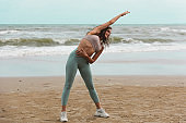 Healthy sport women stretching body warm up before workout outdoor. Athlete in sportswear happy nice resting at the beach. Exercise to prevent the coronavirus and new normal concept